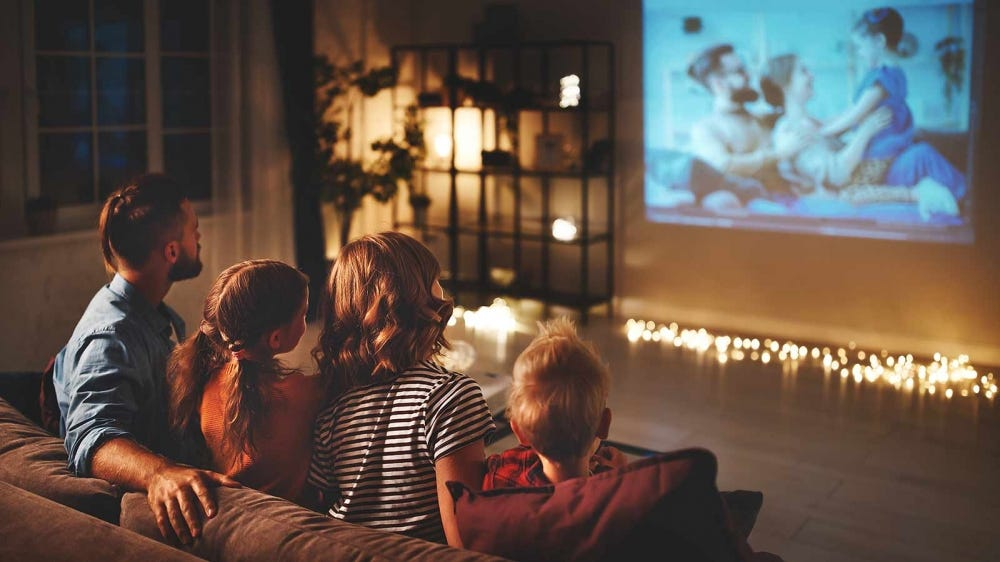 Family watching a movie, projected onto the wall of their living room.