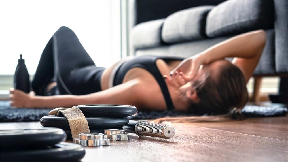 Woman laying on the floor next to workout equipment in her home.