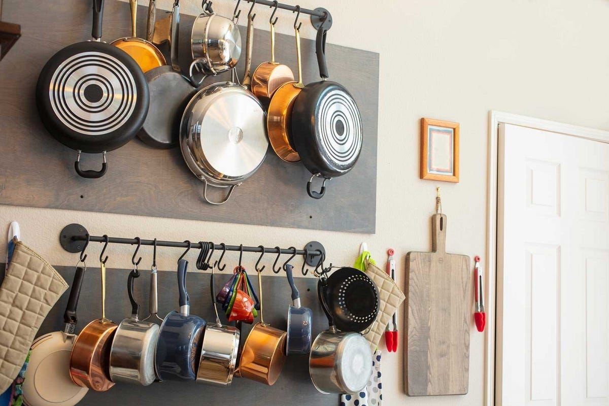 Two rows of Pots and Pans hanging on curtain rods that are attached to a wall.