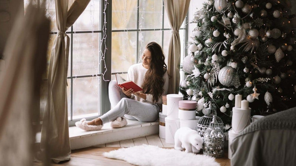A woman reading a book on a window seat beside a Christmas tree.