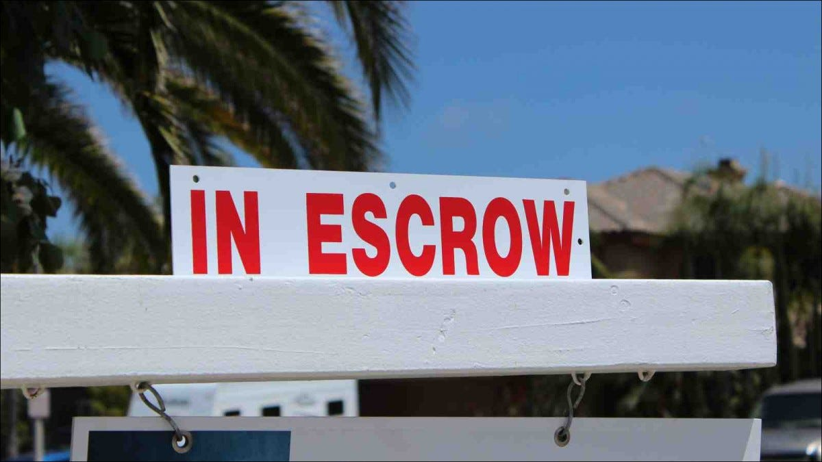 "Close up of a sign ""in Escrow"" on a home sold"
