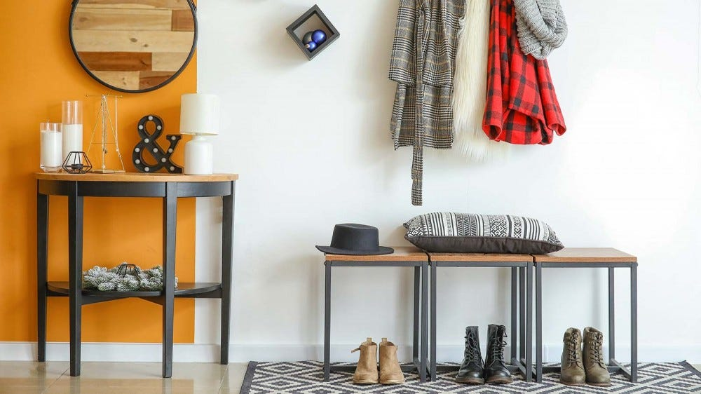 A foyer with three pairs of boots sitting under a bench and coatrack