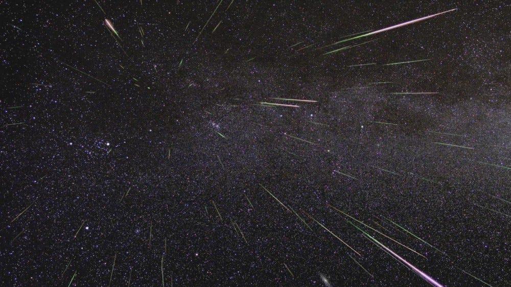 Meteors streak through a dark, starry sky.