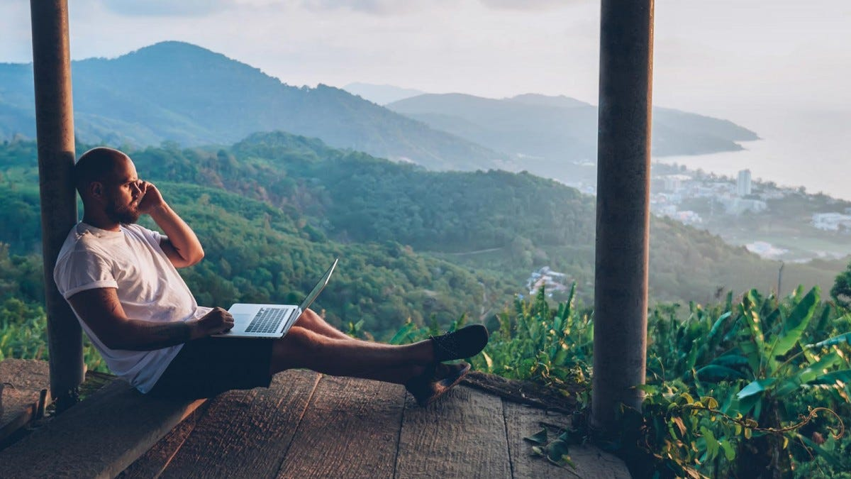 A man with his cell phone to his ear, holding a laptop, as he sits on a porch overlooking a mountainous landscape near water.
