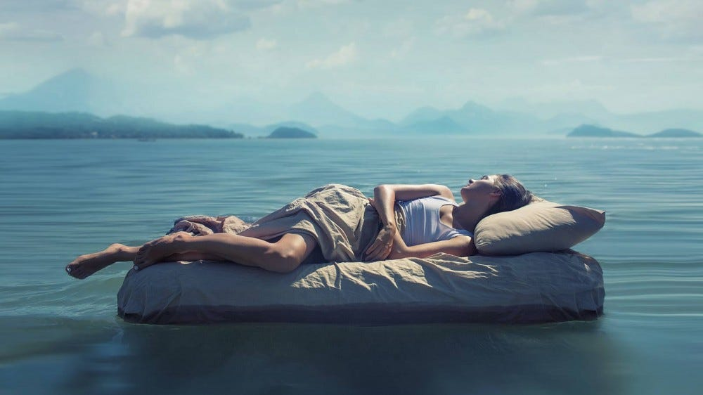 Woman sleeping on a bed floating out on a lake in a dreamy haze.