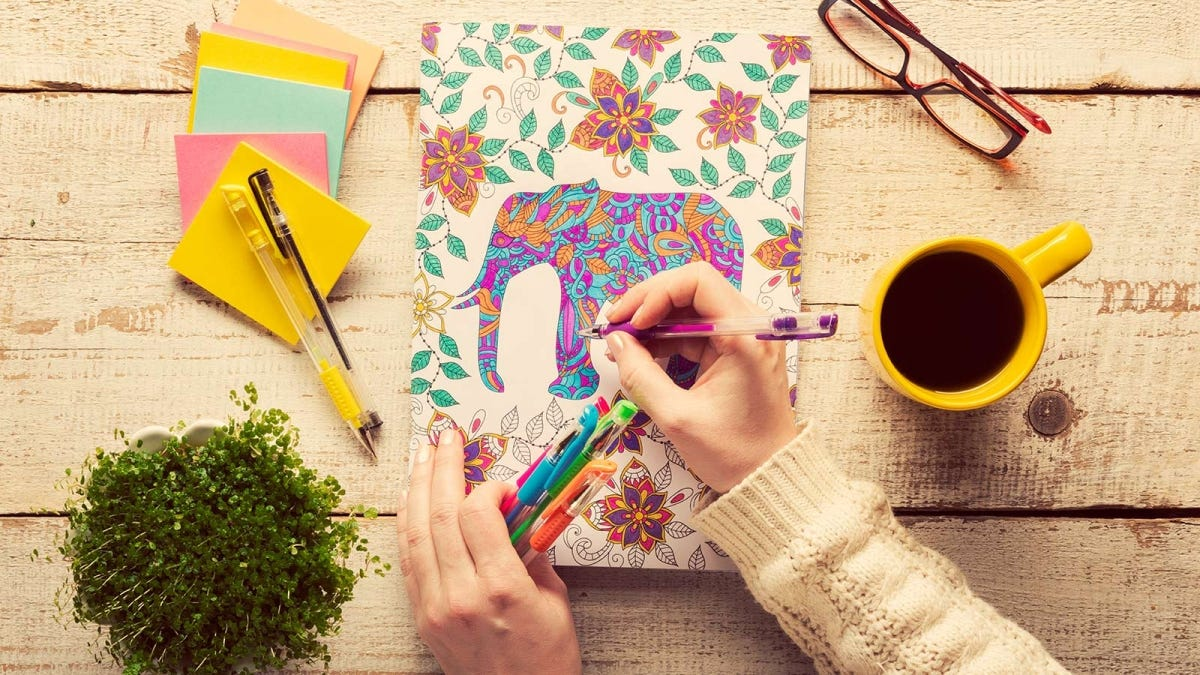 Woman coloring in an adult coloring book with colored pens.