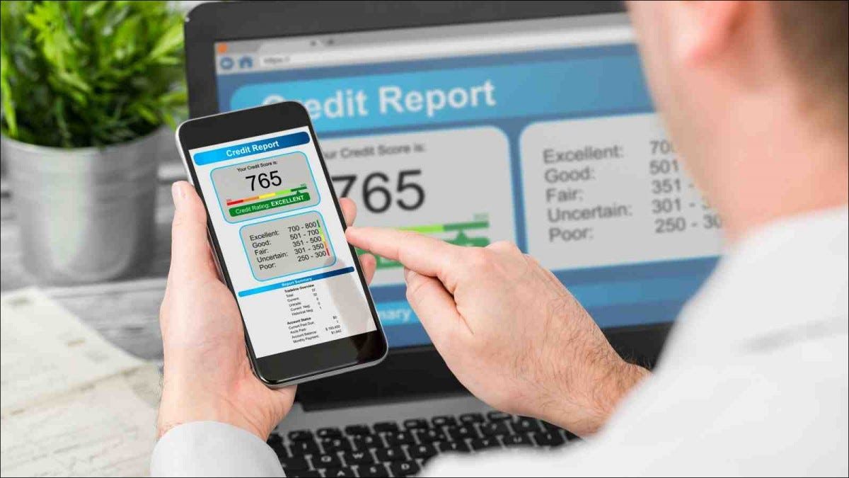 man checking credit score on smartphone and laptop