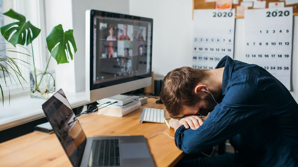 An exhausted man resting his head on his arms in front of his computer during a video call.