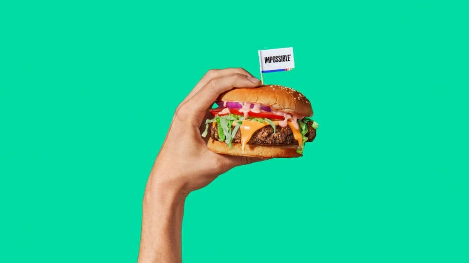 A hand holding an Impossible Burger