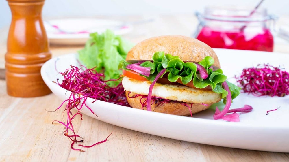 A halloumi burger with lettuce, tomato, pickled red onion and beet sprouts.