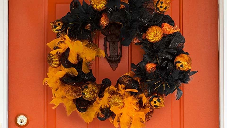 An orange and black jack-'o-lantern wreath made from Dollar Tree craft supplies.