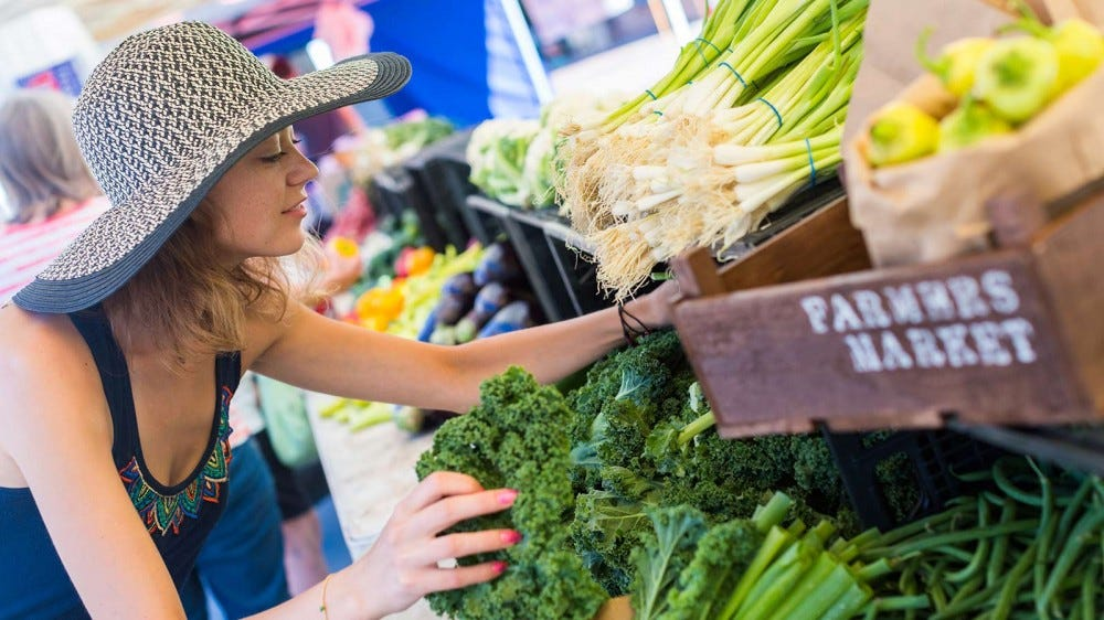 A woman wearing a sun hat picking out fresh produce at the local farmer's market.