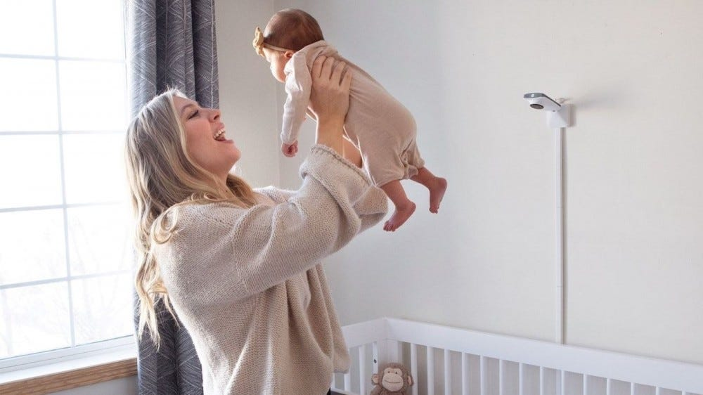 A woman holding a small baby next to a crib with the Miku Smart Baby Monitor above it.