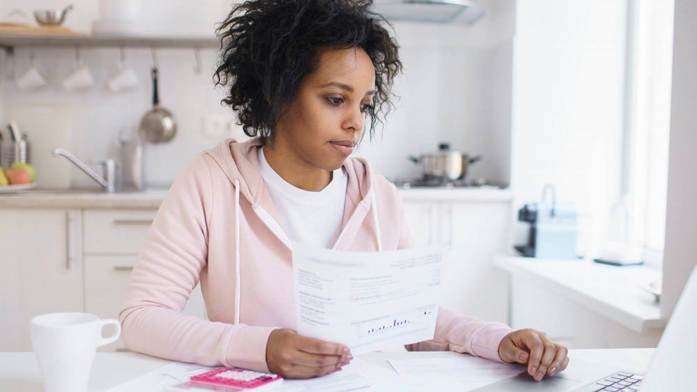 A woman looking at student loan documents and a laptop, planning to pay off her debt.