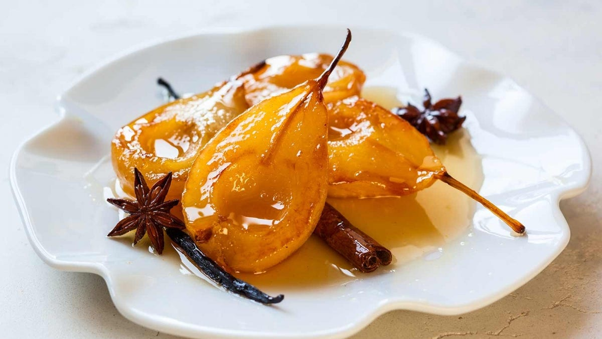 poached pears with spices on a white plate
