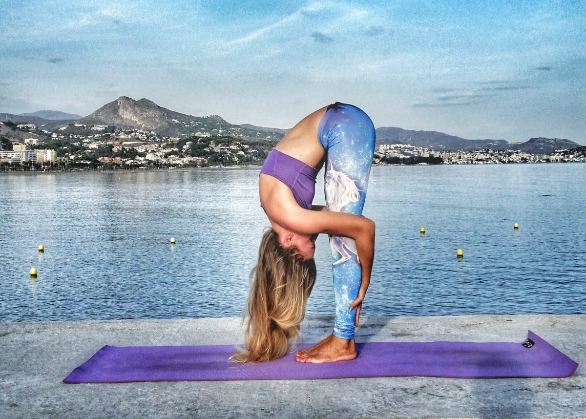 A woman doing a forward fold on a yoga mat by the sea.