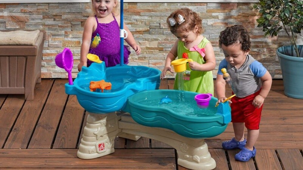 Three toddlers playing with the Step2 Spill and Splash Seaway Sand and Water Table.