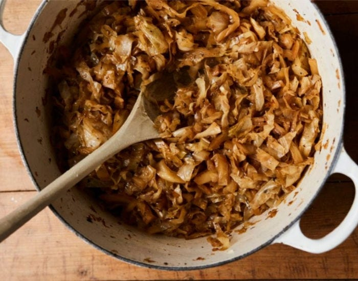 A pot filled with beer braised cabbage with a wooden spoon inside