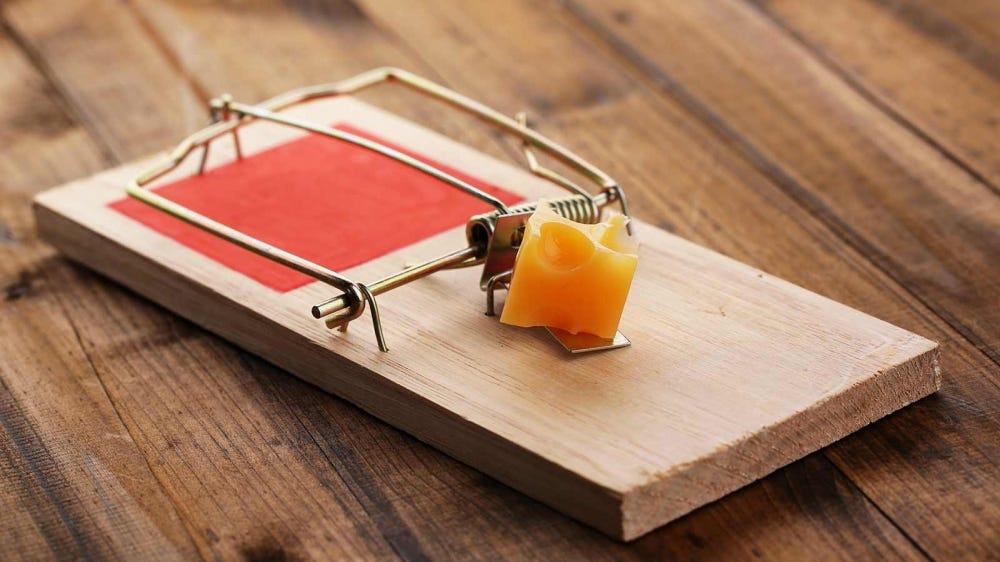 A mousetrap loaded with cheese.