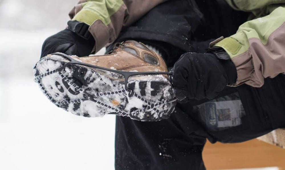 A man removing a snow-covered traction plate from his shoe.