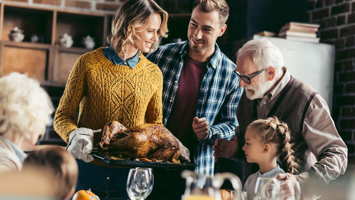 woman bringing a turkey to the table to be carved, surrounded by family