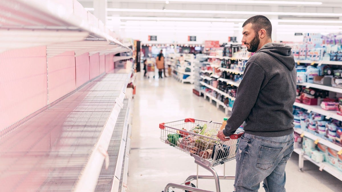 Man shopping for essentials at a store with bare shelves.