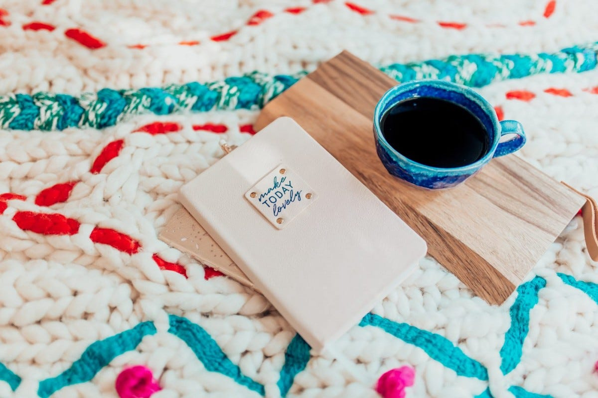Beautiful notebook and tea on a colorful blanket