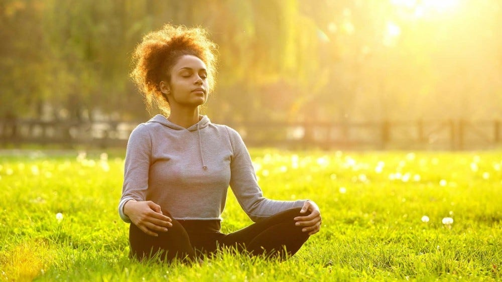 A woman sits in the park at sunrise with her legs crossed and hands on her knees in meditation.