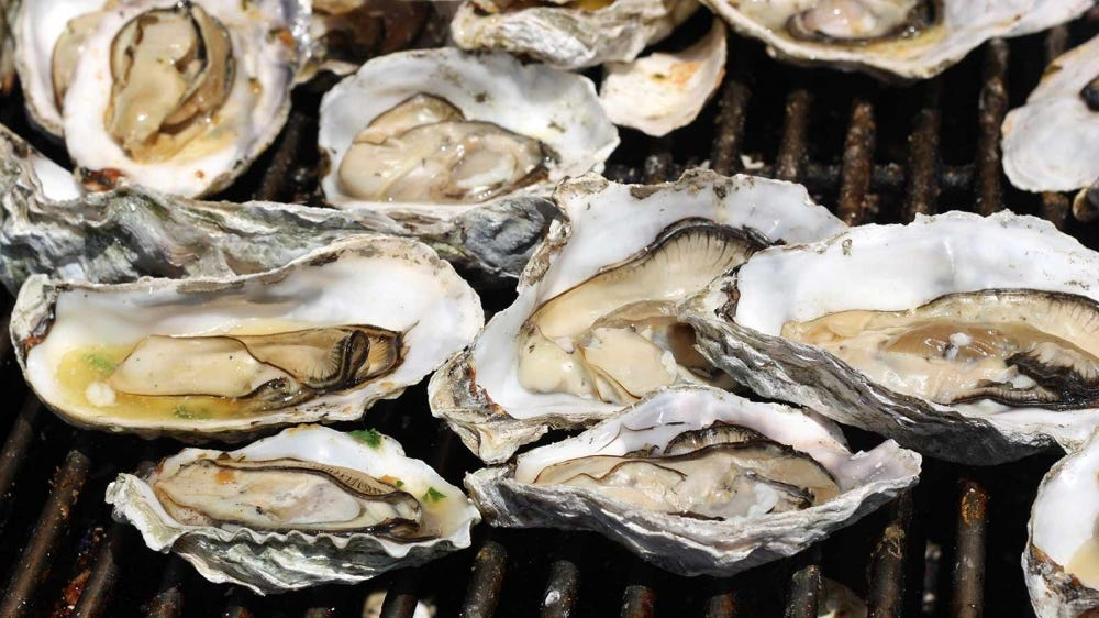 A bunch of oysters on a grill.