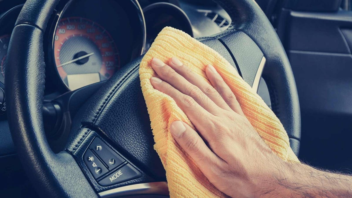 A person wiping down their steering wheel with a microfiber rag.