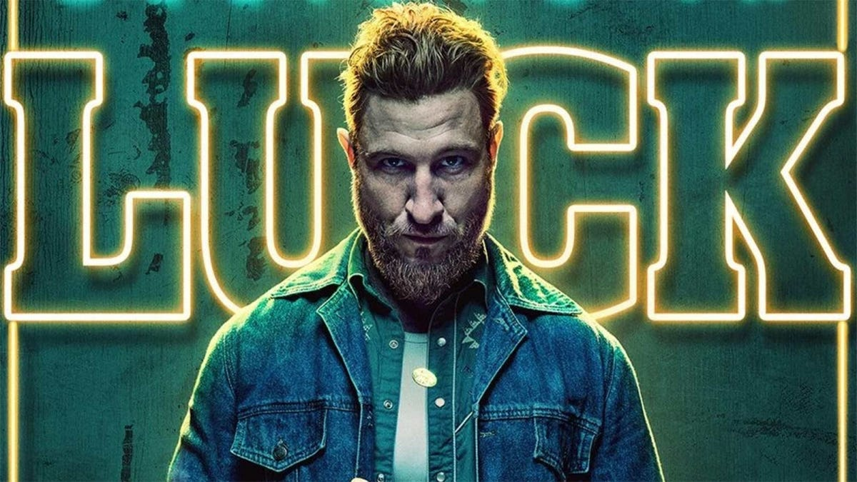 "Mad Sweeney, a character from American Gods, standing in front of a neon sign that says ""Luck."""