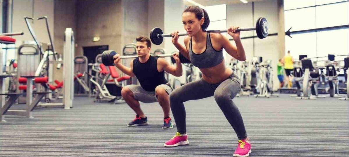young man and woman doing shoulder press squats at gym