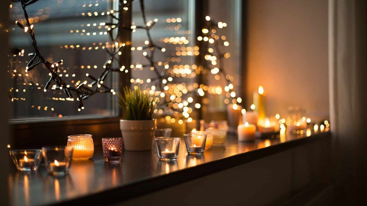 An apartment windowsill loaded with candles and drapped with Christmas lights.