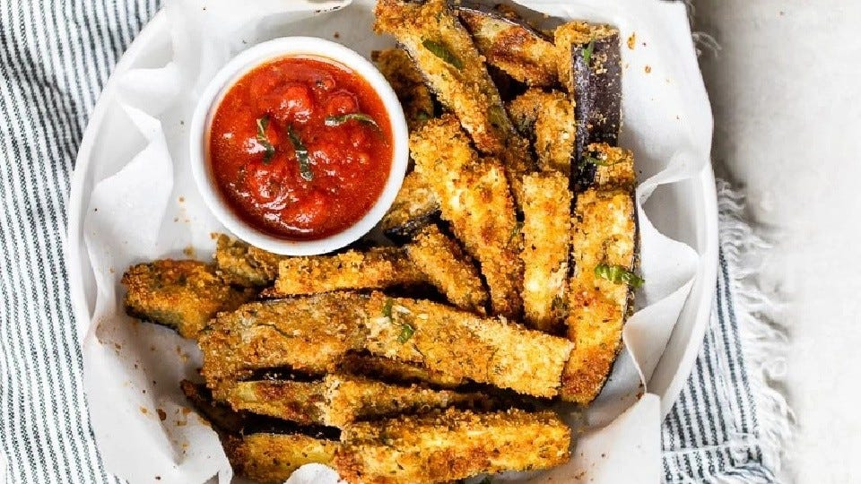 A bowl lined with parchment paper, filled with air fried eggplant sticks with a side of marinara sauce.