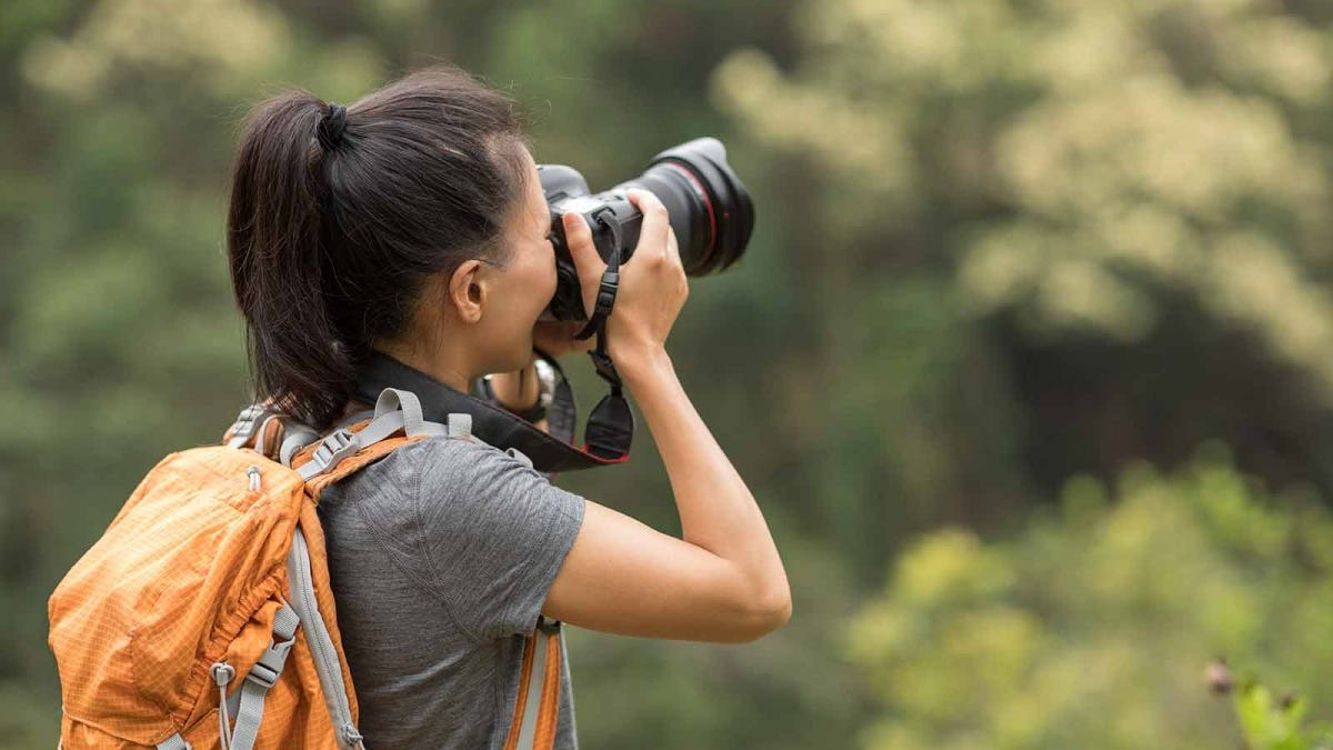 Woman taking nature photos outside with a telephoto lens