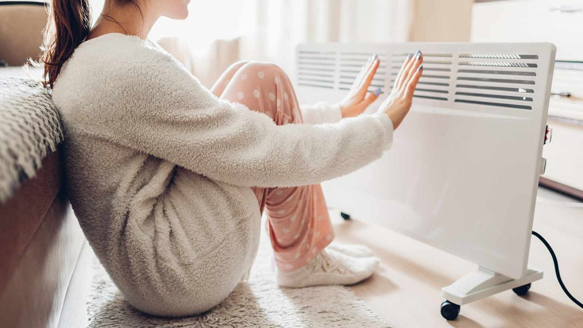 woman huddled in front of an electric space heater trying to keep warm
