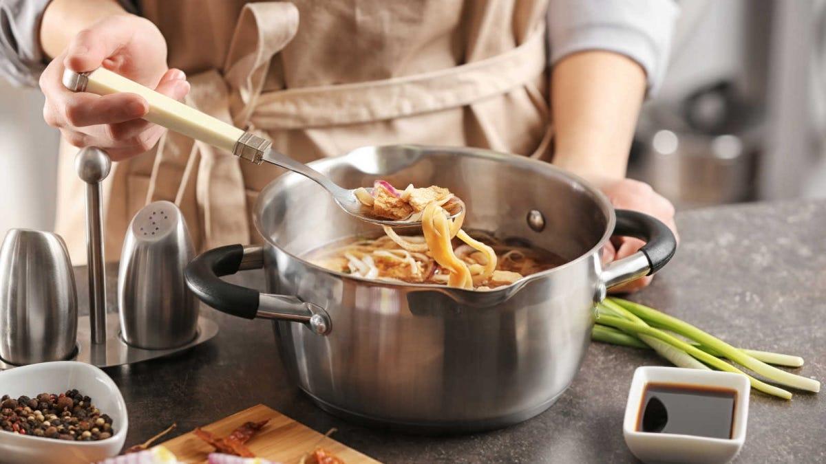 woman seasoning a big pot of chicken noodle soup