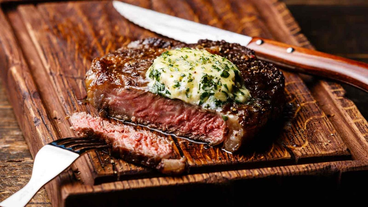 a rich herb compound butter melting atop a juicy steak