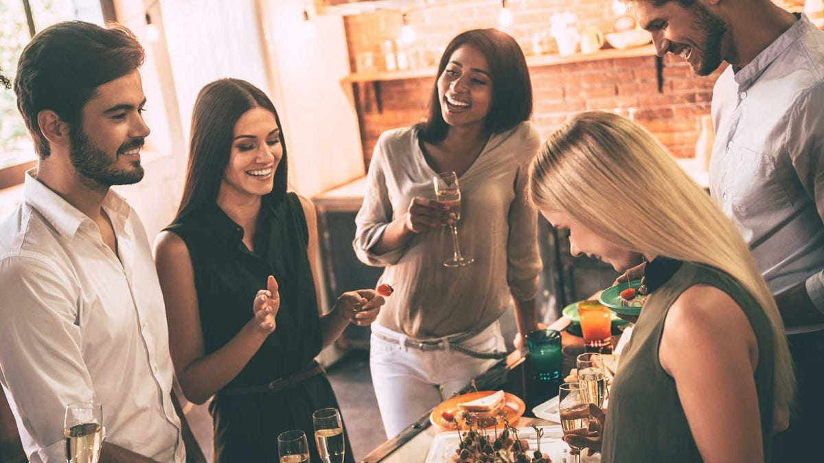 Friends gathered around a buffet full of food holding glasses of wine.