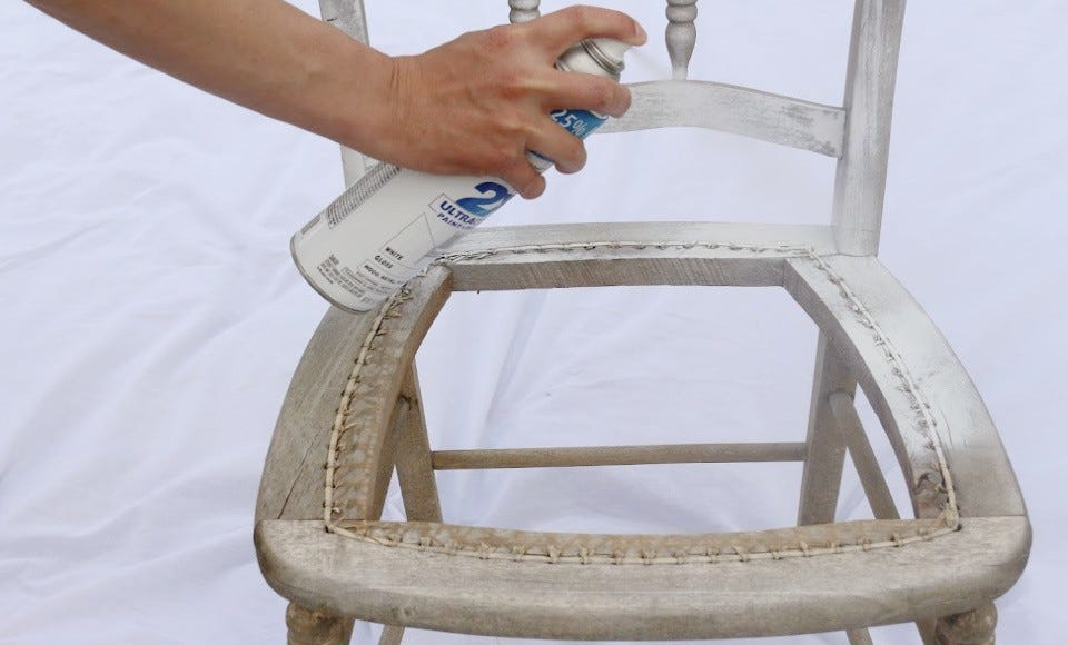 Someone spray painting a chair with white spray paint.