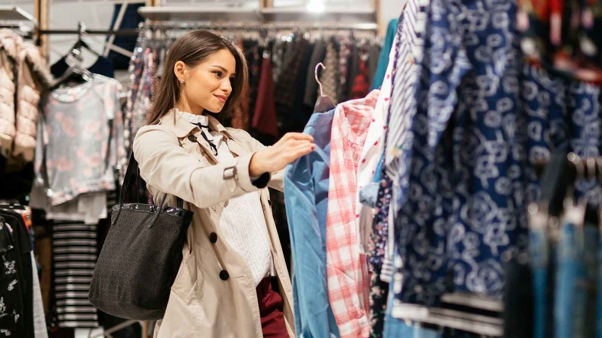 woman looking at an outfit she'd like to buy