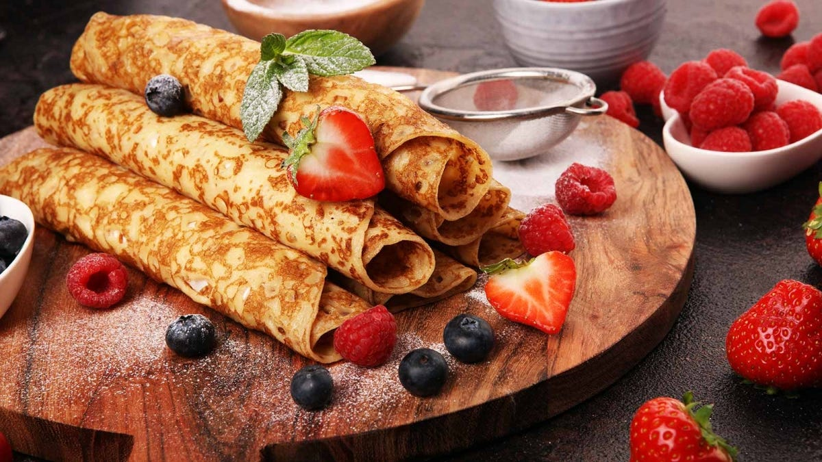 A pile of delicious rolled up crepes on a cutting board.