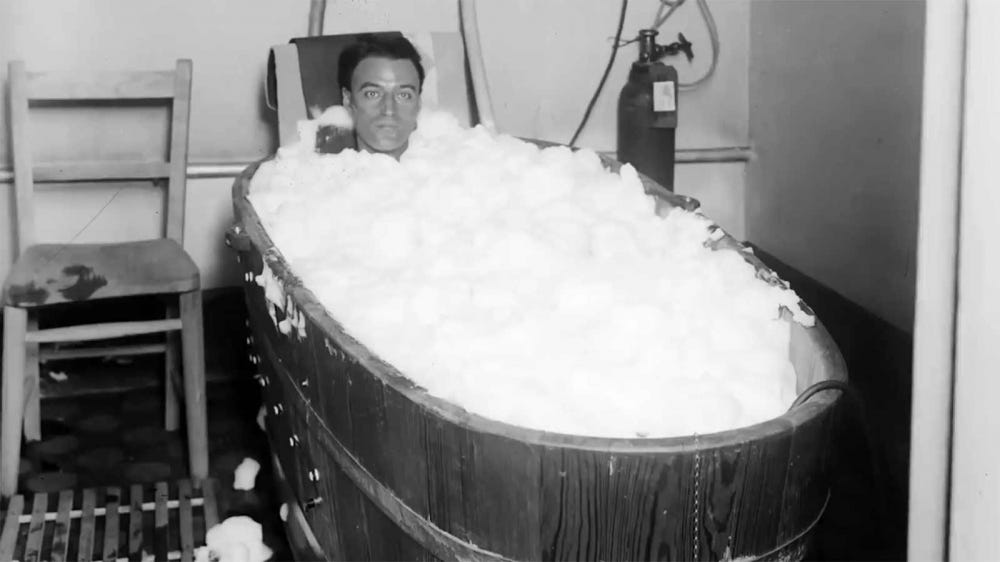 A man bathing in an early wooden bathtub.