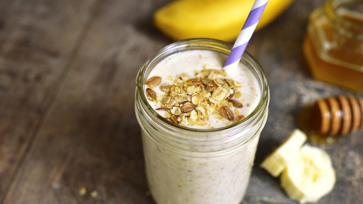 A mason jar with a banana smoothie in it.