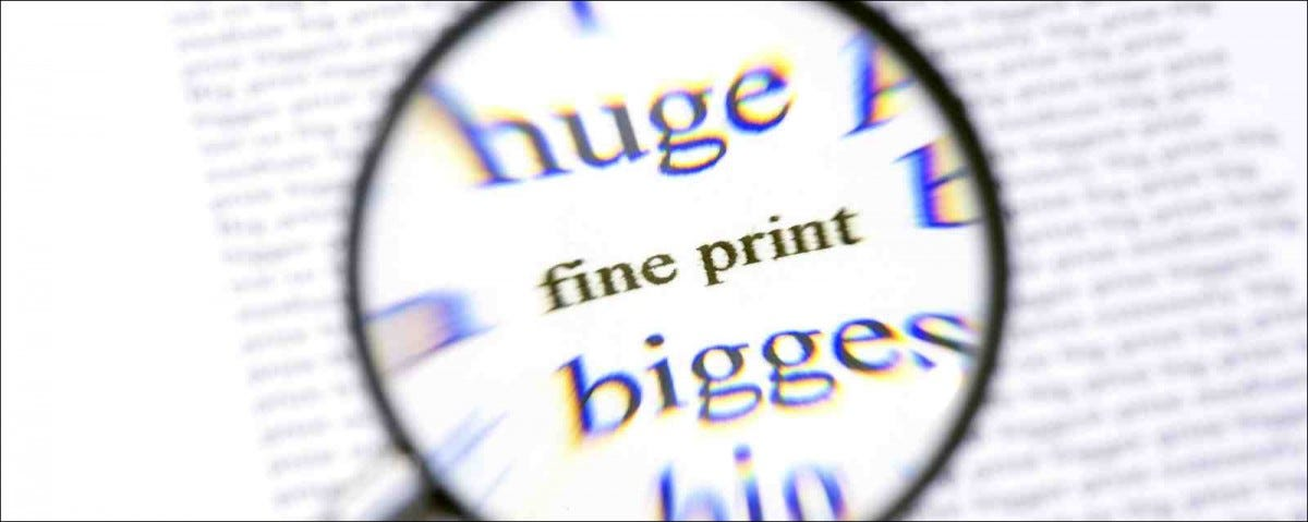 A magnifying glass, zooming in on the text Fine Print on a sheet of paper
