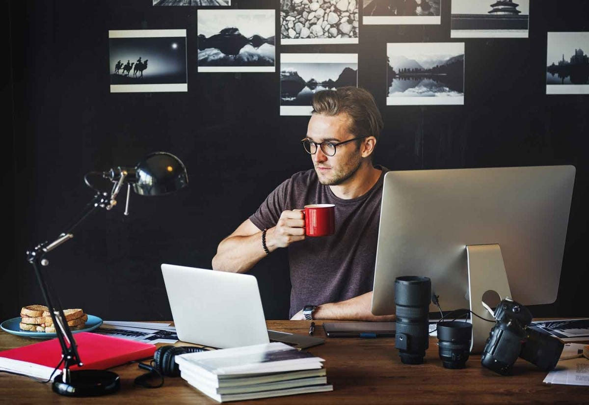 A man sitting at a desk behind a desktop computer screen and a laptop, holding a coffee mug.