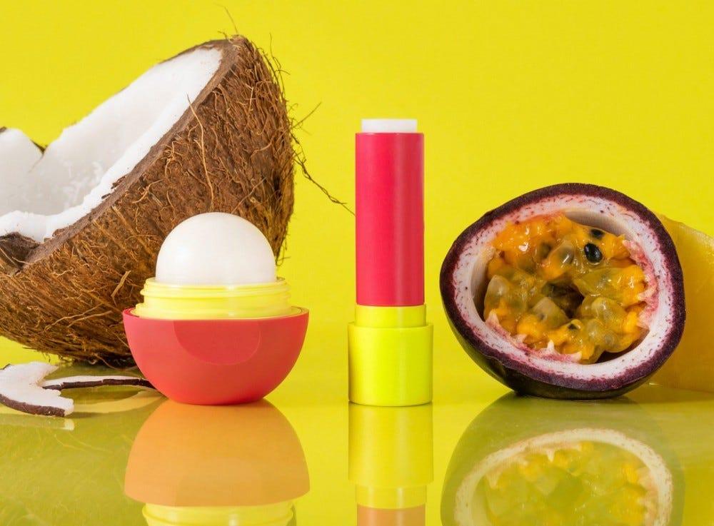 مرهم لبهای رنگارنگ eos در کنار نارگیل و میوه شور قرار دارد.