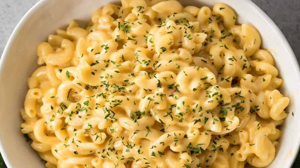A bowl of macaroni and cheese topped with chopped parsley.