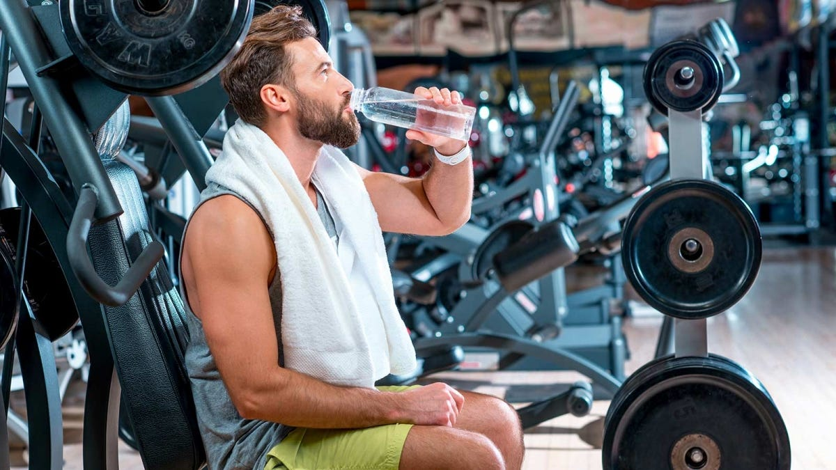 Man drinking water between workout sets at the gym.