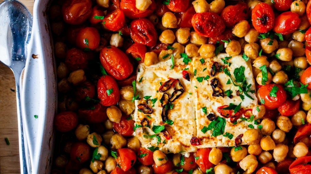 A platter full of chickpea baked feta with two pieces of focaccia.